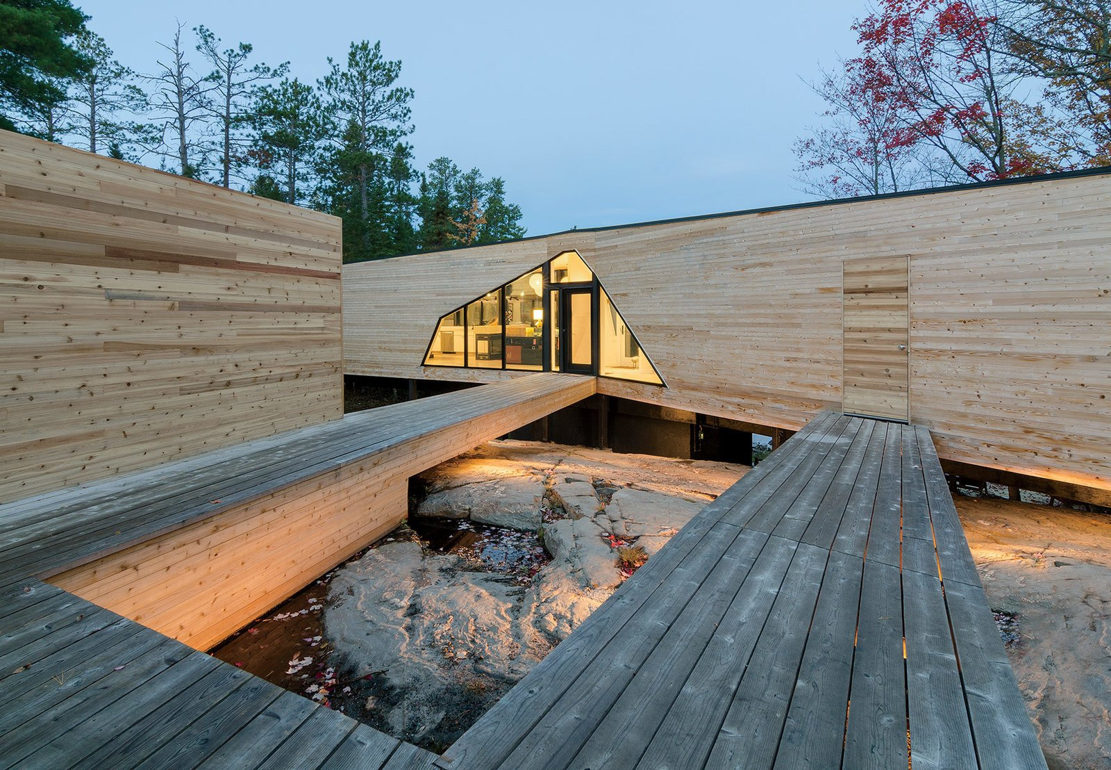 The three-bedroom home is connected to a dock house, garage, and vegetable garden by a network of wood walkways and decks. Tagged: Outdoor, Wood Patio, Porch, Deck, and Large Patio, Porch, Deck.  Photo 2 of 3 in Prefab Made This Super Remote House in the Ontario Wilderness Possible