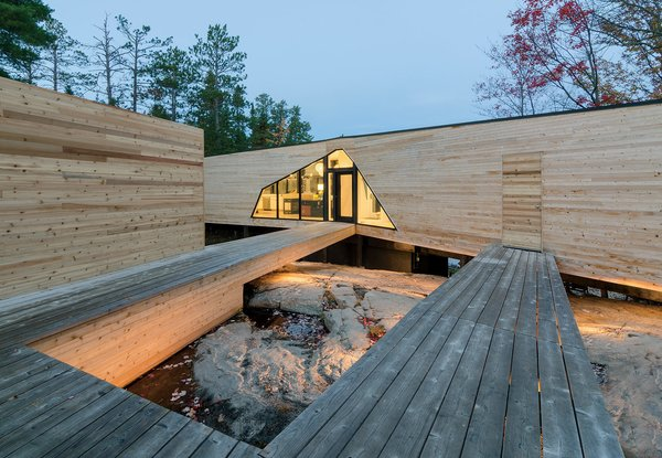 The three-bedroom home is connected to a dock house, garage, and vegetable garden by a network of wood walkways and decks.