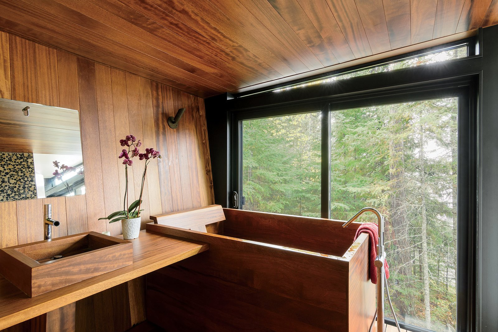 The Japanese-style bathroom, which is clad in teak, features a matching tub and sink by Bath in Wood. Tagged: Bath Room, Vessel Sink, Soaking Tub, Wood Counter, and Medium Hardwood Floor.  Photo 4 of 14 in Inspired Indoor Teak Looks from Prefab Made This Super Remote House in the Ontario Wilderness Possible