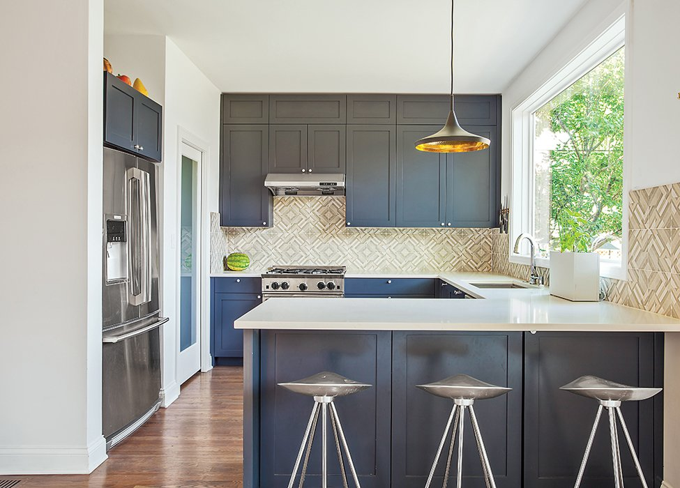 The kitchen sports blue-gray cabinets and Azulej tiles by Patricia Urquiola for Mutina. The Currys keep an eye on the backyard through a large Pella window, situated above a sink with a Sensate faucet from Kohler. The range is by BlueStar. Tagged: Kitchen, Pendant Lighting, Range Hood, Refrigerator, and Medium Hardwood Floor.  Photo 4 of 6 in This Farmhouse-Style Home Gets a Clever and Geometric Update