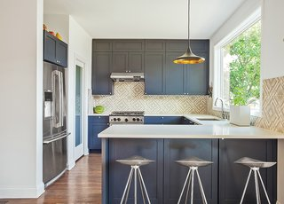 This Farmhouse-Style Home Gets a Clever and Geometric Update - Photo 3 of 5 - The kitchen sports blue-gray cabinets and Azulej tiles by Patricia Urquiola for Mutina. The Currys keep an eye on the backyard through a large Pella window, situated above a sink with a Sensate faucet from Kohler. The range is by BlueStar.