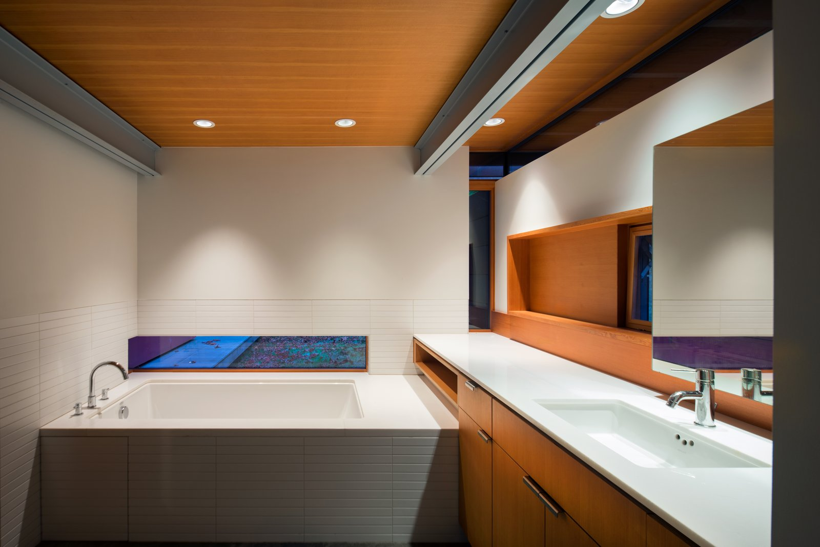 A horizontal sliver of window allows light into the bathroom, with tile by Ann Sacks, a Zuma Collection C Series tub, a Kohler tub filler, and an Elkay faucet.  Photo 13 of 16 in An Off-the-Grid Island Home for a Seattle Music Producer