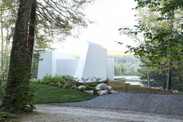 """As the home is approached from the street, the white aluminum facade projects out from the earth in an abstract composition of forms and volumes. There are no doors or windows at the entrance from the road, a calculated decision by the design team to avoid a structure that would read as manmade against the natural landscape. """"We wanted it to feel 'non-architectural' in a way so that the natural view of the lake was not walled off by a privatized notion of someone's home,"""" says Miller."""