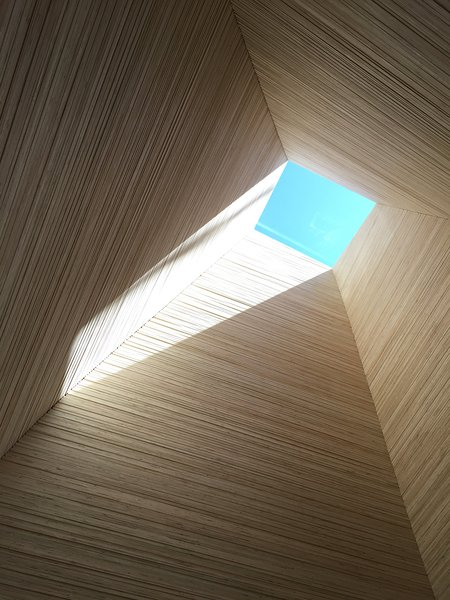 """At the entry looking upward towards a Velux skylight, a vertical """"sleeve"""" is made of stacked end grain plywood. The theme of vertical and horizontal architectural elements providing different environmental perspectives carries through to the rest of the home. Horizontal forms look out to the lake, while the vertical columns look up the sky."""
