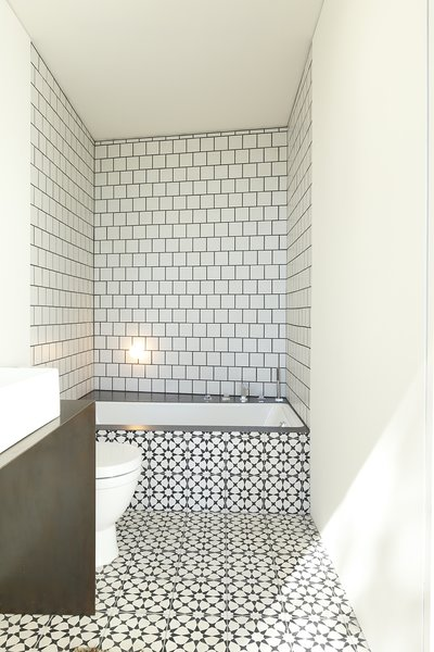Part of the master suite, the bright bathroom embraces texture and pattern. The space clad in bold, graphic tile and features a custom steel vanity.