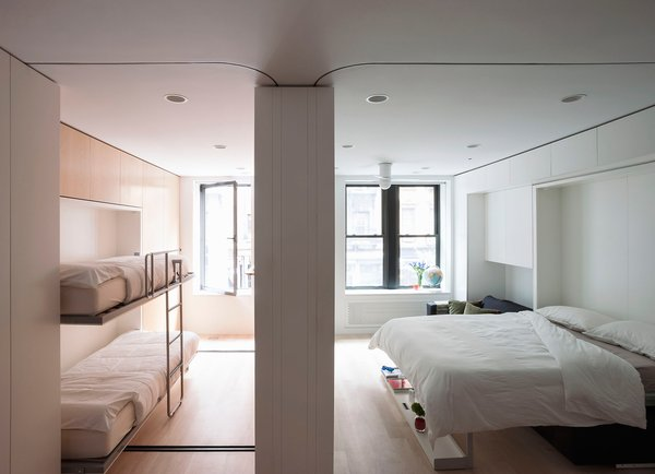This concept apartment presented by LifeEdited in SoHo shows how much one can fit in 420 square feet. Murphy beds make it possible to sleep four. When they're not in use, a large dining table can be pulled out. Heavy red curtains pull out of the walls to enclose each room for maximum privacy and sound control.