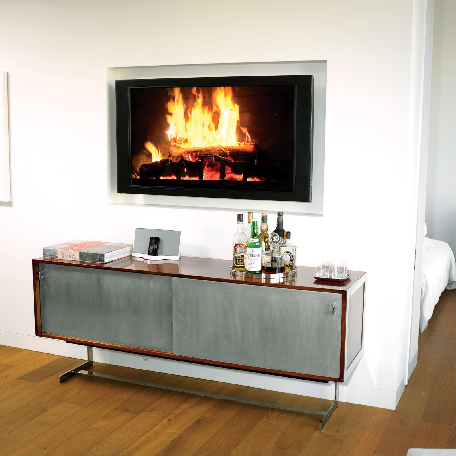 "No room for a built-in bar? Wing it, like architect Cass Calder Smith did in his SoHo apartment, with a modern cabinet, trays to hold bottles and glasses, and a roaring ""fire.""Photo by   Brian Finke.  Photo 6 of 14 in High-Rise Living in Manhattan"