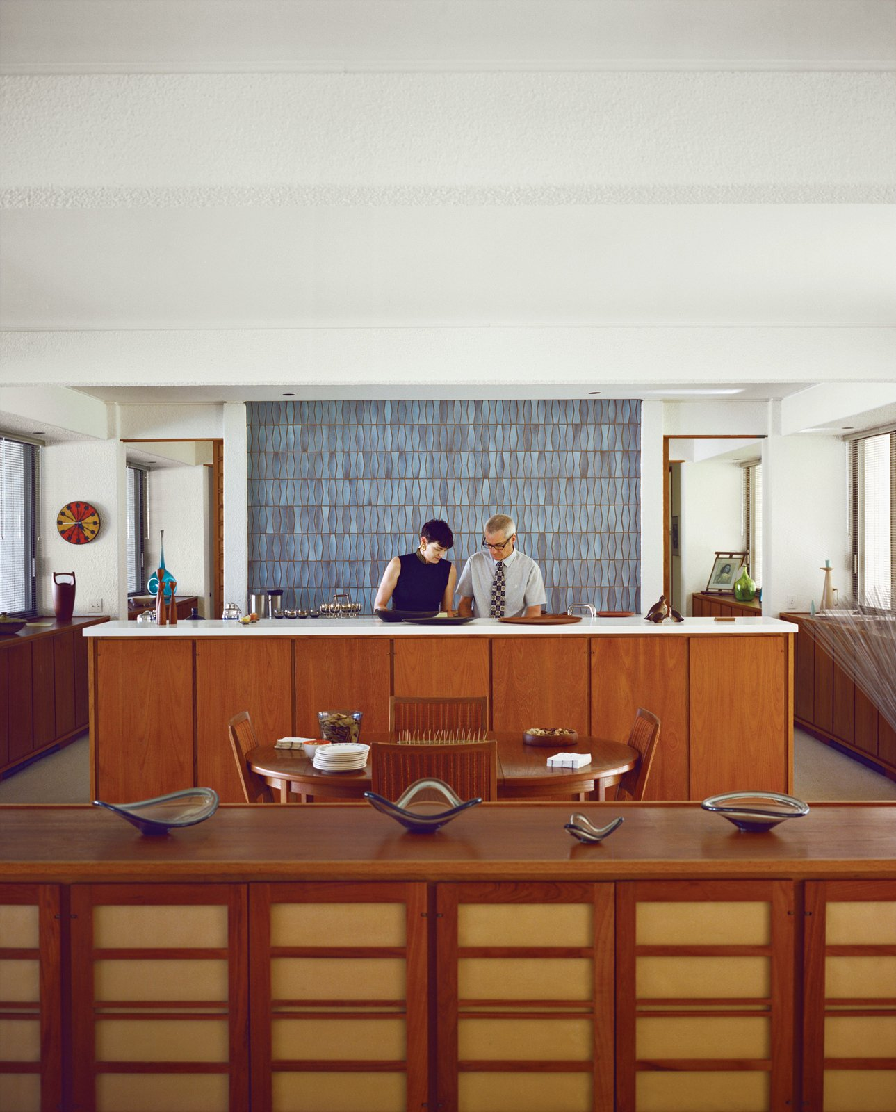 Stacey and Doug prepare food before the kitchen's massive wall of soothing tile from Heath Ceramics. Tagged: Kitchen, Wood Cabinet, and Ceramic Tile Backsplashe.  Best Photos from Modern Home in a California Resort Town