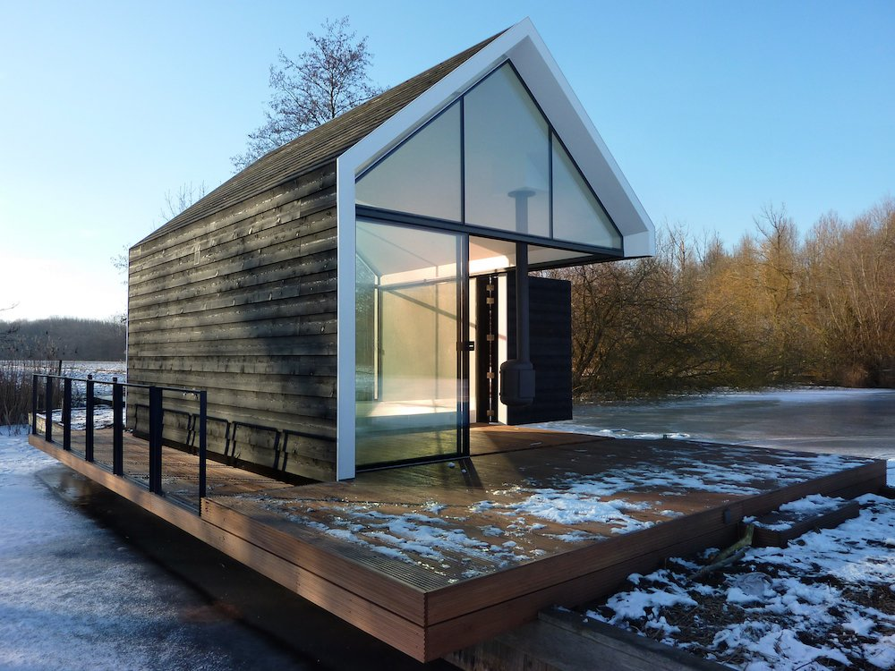"Utilized year-round, the 225-square-foot cabin opens up to the surrounding countryside via parallel glass walls on either end and a folding wood door that leads to the terrace. Co-designer Remko Remijnse of 2by4 Architects says the concept was to make the ""natural surroundings become part of the living room [so] you have endless living space."""