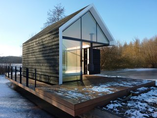 """Sourcing Guide for Modern Prefab Companies in Europe - Photo 1 of 11 - Utilized year-round, the 225-square-foot cabin opens up to the surrounding countryside via parallel glass walls on either end and a folding wood door that leads to the terrace. Co-designer Remko Remijnse of 2by4 Architects says the concept was to make the """"natural surroundings become part of the living room [so] you have endless living space."""""""