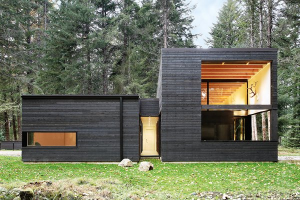 """""""The cedar siding is simply stained with a black semi-transparent oil stain [from Cabot], which allows the color of the wood to still emerge through,"""" architect Robert Hutchison says. """"We love how the black color makes the building recede into the background, and how it in turn allows the trees on the site to emerge as the highlight."""""""