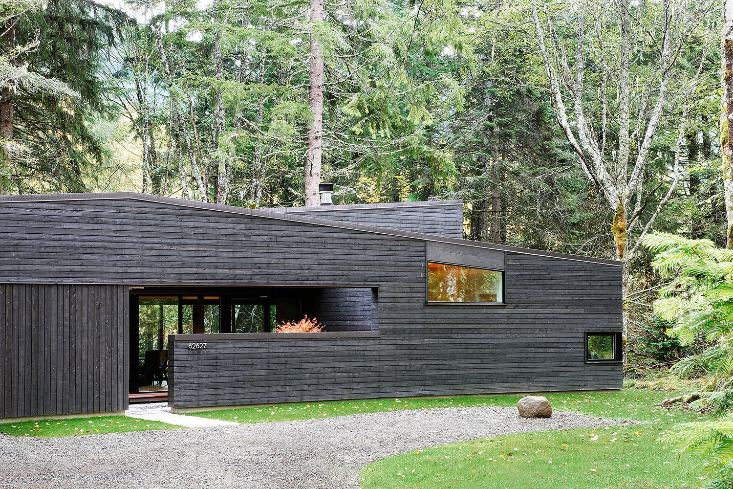 """From the street, it appears as a rectangular building with sloping shed roofs, but this is actually an illusion,"" Hutchison notes. ""The floor plan is actually U-shaped, wrapping around an entry courtyard that is contained by the continuous west facade."" A standing seam metal roof by Custom Bilt Metals blends in with the cedar siding. Tagged: Exterior, House, Cabin Building Type, and Wood Siding Material.  Photo 94 of 101 in 101 Best Modern Cabins from Courtyard House on a River"
