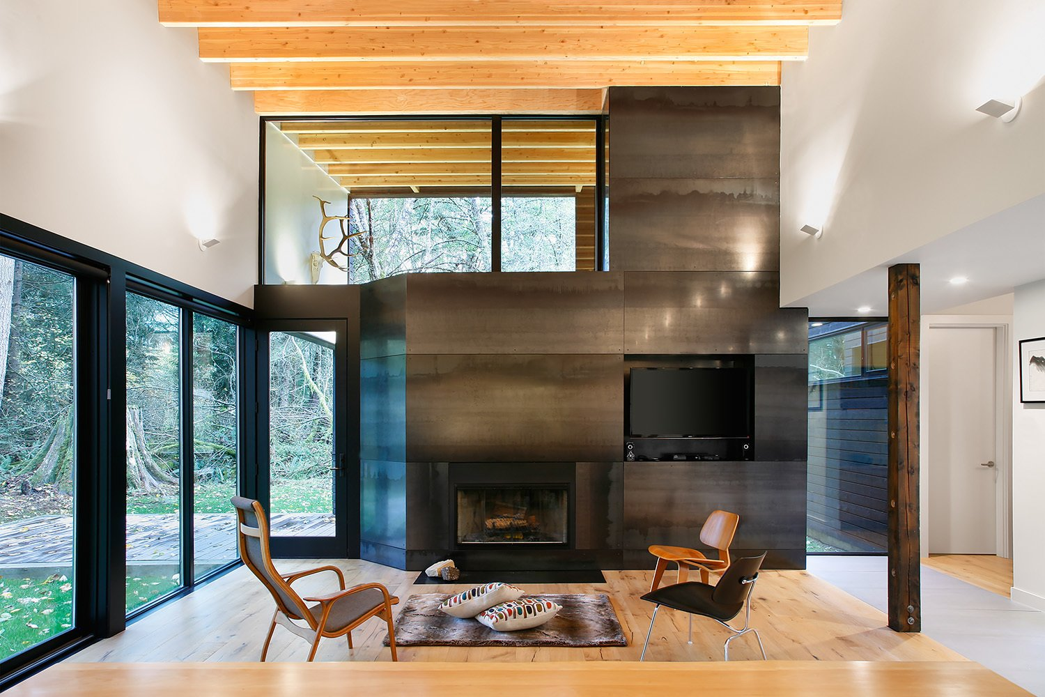 """""""From the courtyard, you then enter the house proper, directly into the main living room,"""" Hutchison says. """"From this room, you have a panoramic view looking out through the trees to the river, or back into the courtyard."""" The wood-burning fireplace, from Majestic, is clad in steel panels. Eames Molded Plywood lounge chairs sit side-by-side in the living room.  Courtyard House on a River by Kelly Dawson"""