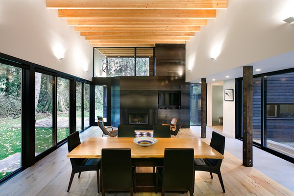 """The home's interior design was intentionally simple: access to light and views were a main priority. """"The roof in this room slopes gradually up to the south, providing a light monitor that brings in southern light filtered through the trees, while providing a framed view of the tops of the trees beyond,"""" Hutchison says. Plank flooring by United Tile and Edge wall sconces by Belfer unite the living and dining spaces. Photo 5 of Courtyard House on a River modern home"""