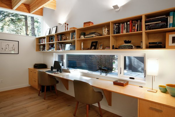 """""""The roof structure is exposed in every room of the house, which leads the eye to connect all of the rooms together, making the house seem bigger than it really is,"""" Hutchison says. Dunn Lumber supplied the laminate shelves for the study. Photo 6 of Courtyard House on a River modern home"""