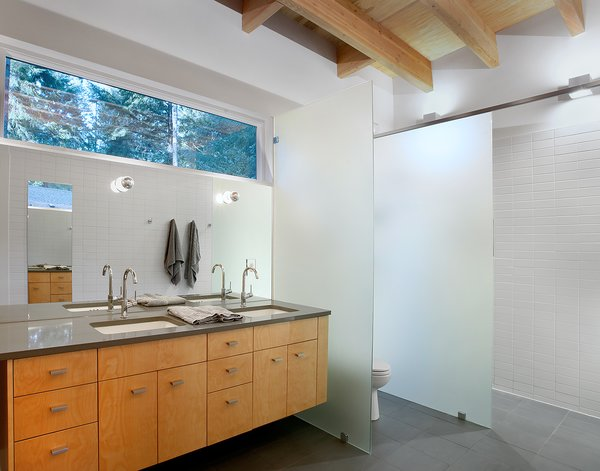 Matching Ladena sinks by Kohler, outfitted with Talis S faucets by Hansgrohe, stand inside polished Stormy Sky countertops by PentalQuartz. Photo 7 of Courtyard House on a River modern home