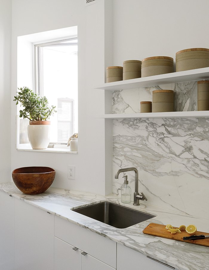 How One Family of Three Does It All in 675 Square Feet - Photo 3 of 14 - The showstopping material elements are the Borghini honed marble countertop and backsplash by Ann Sacks. Hasami porcelain vessels line the open shelving.