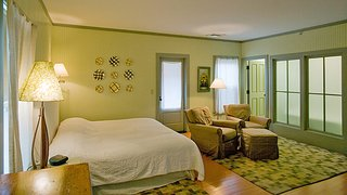 Porches Inn, North Adams, Massachusetts - Photo 6 of 21 - With four primary color schemes featured, headboard walls are painted terra cotta, pale blueberry, celery green, and sage green to complement wooden floors painted olive green, red, pumpkin and buttercup.<br><br>As part of her creative process Fitzpatrick conceptualized the design for each room by first establishing its color combination, and then matched vintage and modern pieces to accentuate the hues.