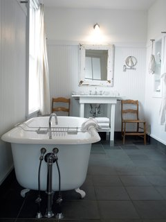 Porches Inn, North Adams, Massachusetts - Photo 12 of 21 - For a luxe evening soak, larger bathrooms (measuring 75-100 square feet) feature either Jacuzzi-style or claw-foot bathtubs with separate showers. The bathrooms also boast slate floors and distinctive touches like frosted glass and mirror frames salvaged from the building's original window frames. Bathrobes and towels hang from metal wall pegs reminiscent of 19th-century Shaker design.