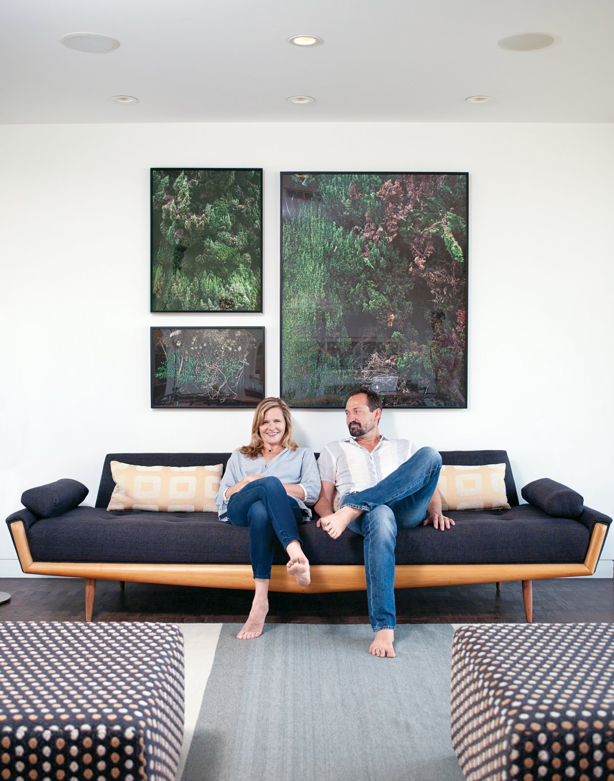 Gabbert and Avery relax on a vintage sofa in their living room beneath large-format photos of juniper bushes by Maegan Hill-Carroll. L-Shaped Indoor-Outdoor LA Home - Photo 1 of 21