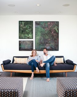 L-Shaped Indoor-Outdoor LA Home - Photo 1 of 21 - Gabbert and Avery relax on a vintage sofa in their living room beneath large-format photos of juniper bushes by Maegan Hill-Carroll.
