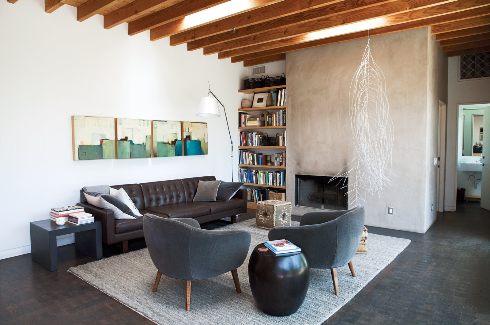 A family room off the kitchen is stocked with pieces from Room & Board, including the Wells sofa and gray Cable rug. The hanging sculpture is by Rebecca Niederlander and the quartet of paintings is by Babak Emanuel. L-Shaped Indoor-Outdoor LA Home - Photo 6 of 21