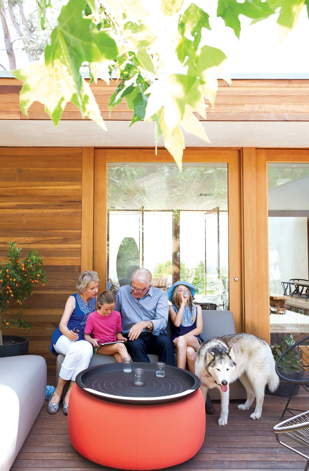 Daughters Ingrid and Jane catch up with their grandparents on the Room & Board–furnished front deck. L-Shaped Indoor-Outdoor LA Home - Photo 8 of 21