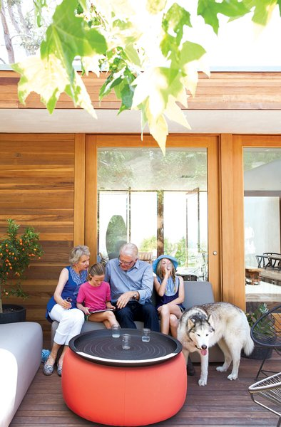 Daughters Ingrid and Jane catch up with their grandparents on the Room & Board–furnished front deck.