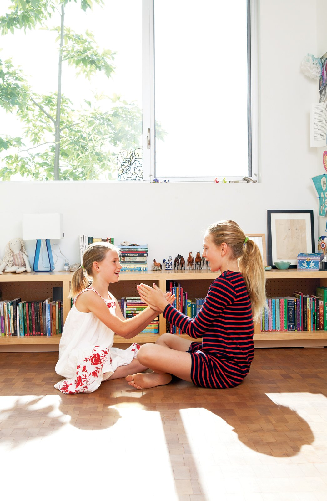 Daughters Ingrid and Jane play on the floor of their bedroom, laid with reclaimed end-grain parquet from Oregon Lumber.  Photo 9 of 21 in L-Shaped Indoor-Outdoor LA Home