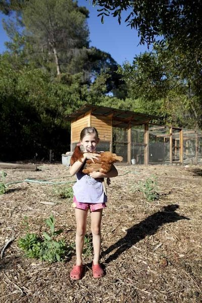 Ingrid shows off one of the chickens the family raises in their large and very productive coop.