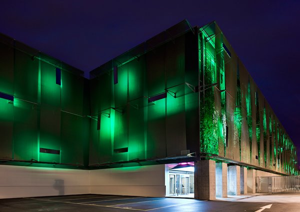 """Singapore Free Port, Exterior, 2010<br><br>Grawunder worked closely with Swiss architects Benedicte Montant and Carmelo Stendardo to light this storage facility, designed as the """"ultimate safe"""" for high-value art and collectibles. On the exterior, Grawunder used very low light green LEDs to give a bioluminescent feeling to the wall of plants behind it. In the daytime, the holes where the light comes from reflect the sky. Containing many kilometers of lights, this is Grawunder's largest installation ever """"and probably will be for a long time,"""" she quips."""