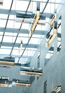"Singapore Free Port, Lobby, 2010 These hanging lights were designed to resemble mirror walls hanging in the lobby space. ""I wanted the mirror effect to reflect the lobby windows and repeat the pattern,"" Grawunder explains. A mirror coating was also applied to the lobby windows, so in the day ""there is a lot of reflection up there."" At night, the ""walls"" glow up and down, with color changing LEDs giving a three-dimensional ceiling effect."