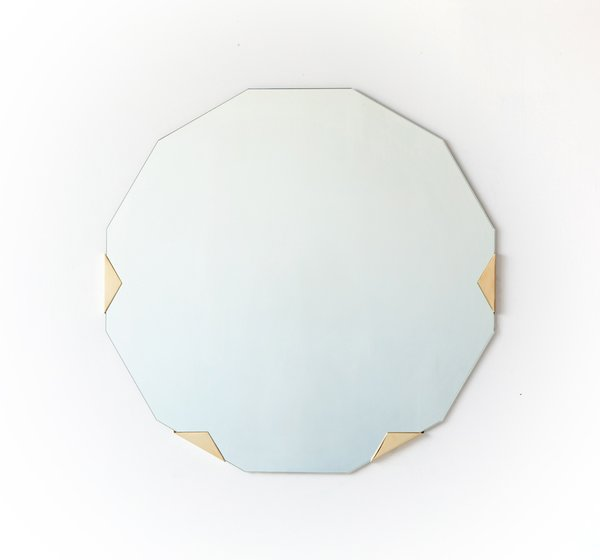"The 12-sided Haynes mirror ($2,800) slips into solid brass or nickel-plated brass brackets. ""Many of our designs are made with materials that will patina over time,"" says Ellis.  ""For example we intentionally don't laquer our brass pieces so that they will age as they are used. We think this speaks to the lifespan of our objects."""