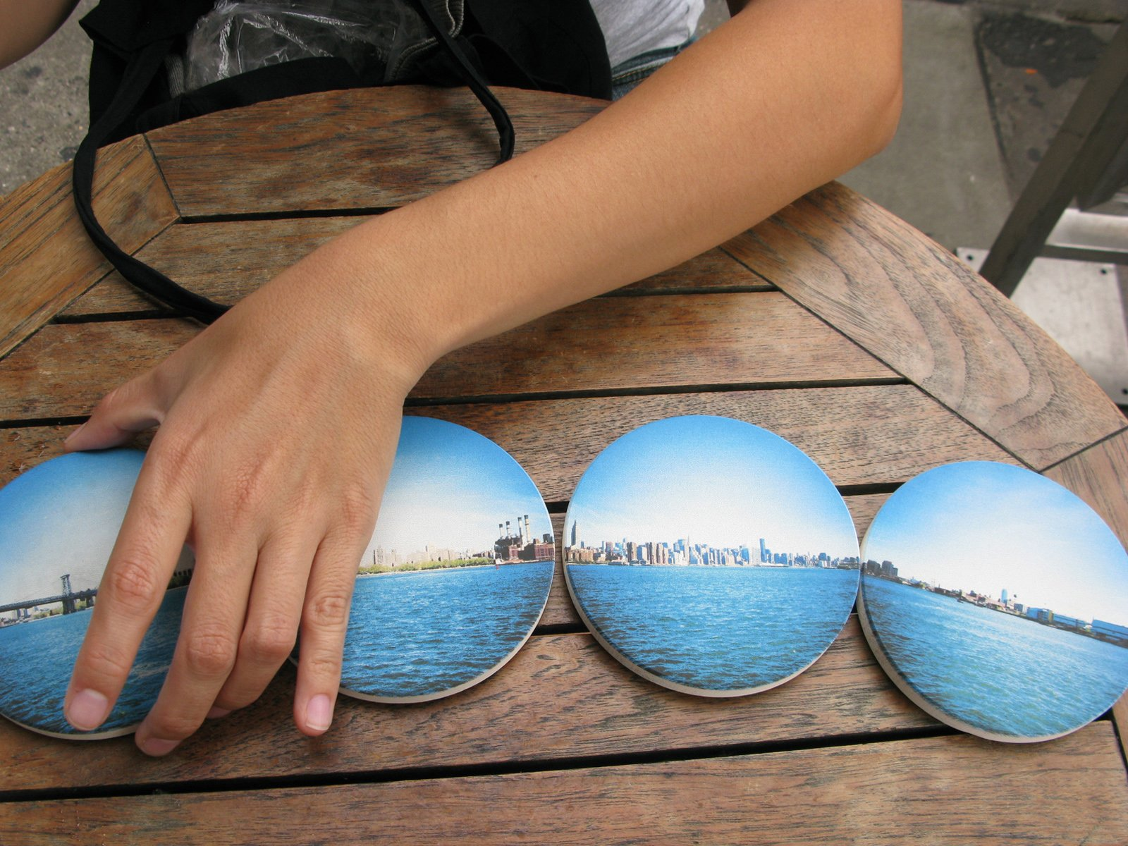 "Tash organizes the ""Brooklyn"" coaster set, an East River panorama."