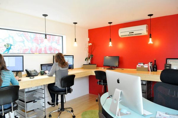 For the realty group interior space, eight people comfortably work in the 12-foot-by-14-foot room. There's a mini slit A/C and heating system, painted sheetrock walls and bamboo floors and desk.
