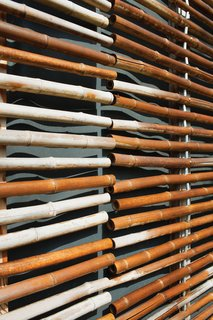 Passive Progressive - Photo 5 of 8 - All told, they hung some 28,000 linear feet of the material with the larger sections composed of around 250 stalks. Each pole is threaded with <br><br>galvanized steel wire and separated from the next by a small aluminum spacer. A highly renewable resource, the untreated bamboo has aged over <br><br>time; what started as yellow-green has turned into a muted gray just a year after completion.