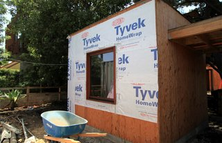 Tyvek wrap and flashing seals the joint between a window and the wall of the front office. Caulking is placed on the interior. Eventually the entire home will be wrapped in Tyvek.