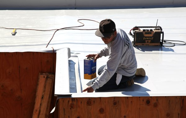 A roof installer from J.T. Harris finishes installing the Versico PVC membrane on a garage roof parapet. The parapet will have a black metal coping installed as the final finish.