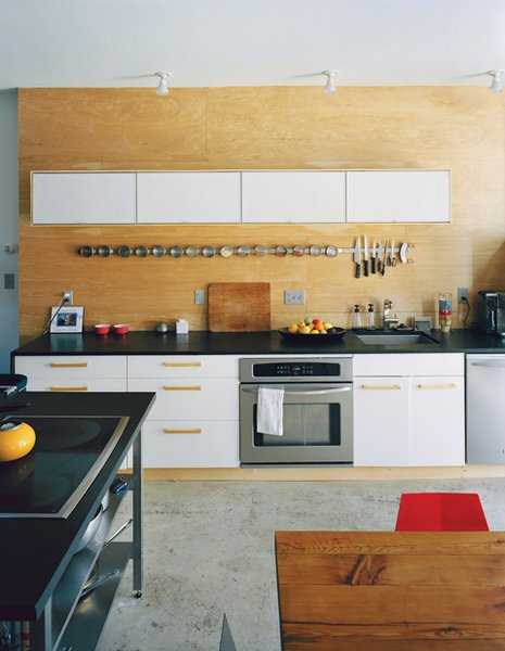 Concrete floors and an Ikea kitchen and spice rack make for an affordable, cleanly geometric aesthetic in the Ludeman's 1,296-square-foot residence, which they built from scratch for just $81 per square foot in construction costs.
