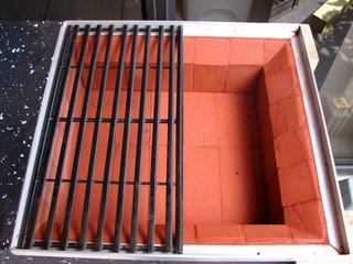 """I used regular mason bricks to cover the grill box and give the granite and outside surface heat protection. I calculated the bricks' thickness to accommodate an aluminum tray to hold the charcoal. The bricks installed on the three sides were cut to 45 degrees at the top to allow the heat to disperse more evenly. I used regular cement with red coloring to hold the bricks in place. For the grill, I selected a pair of rectangle grills to cover the square. I took their size into consideration before developing any other dimensions, so the grill would not have to be modified."""