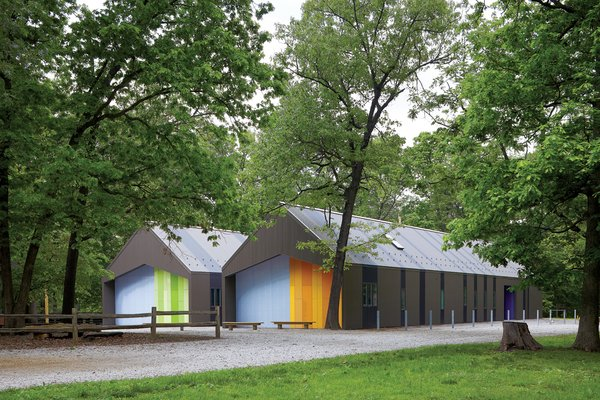 The two-tone corrugated metal cladding helps the sheds blend into the landscape, along with windows custom-colored by the manufacturer to match.