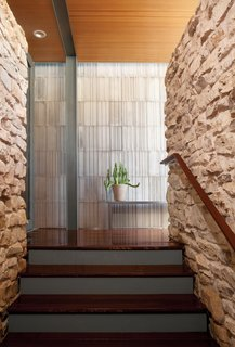Hillside Mid-Century Home Renovation in Texas - Photo 5 of 10 - A striated concrete wall designed by Pollen Architecture & Design contrasts with the rough limestone rock of the home's existing stair column.