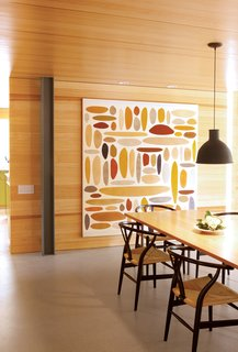 Hillside Mid-Century Home Renovation in Texas - Photo 6 of 10 - An abstract painting by Michael Young complements the glow of the dining room's pine walls. A collapsible silicone lampshade by Swedish designers Form Us With Love for Muuto hangs above a Macek Furniture Company table.