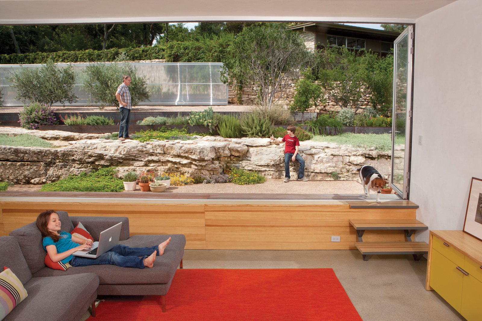 The family room is situated at the apex of the house, with picturesque views that extend   up the meticulously landscaped north slope. The concrete floor sits just low enough that the main elements of the scene—the succulent garden and large limestone ledges—are at eye level. A bank of NanaWall folding windows breaks up the fourth wall. Tagged: Living Room and Sofa.  Photo 7 of 10 in Hillside Mid-Century Home Renovation in Texas from Texas Two-Step