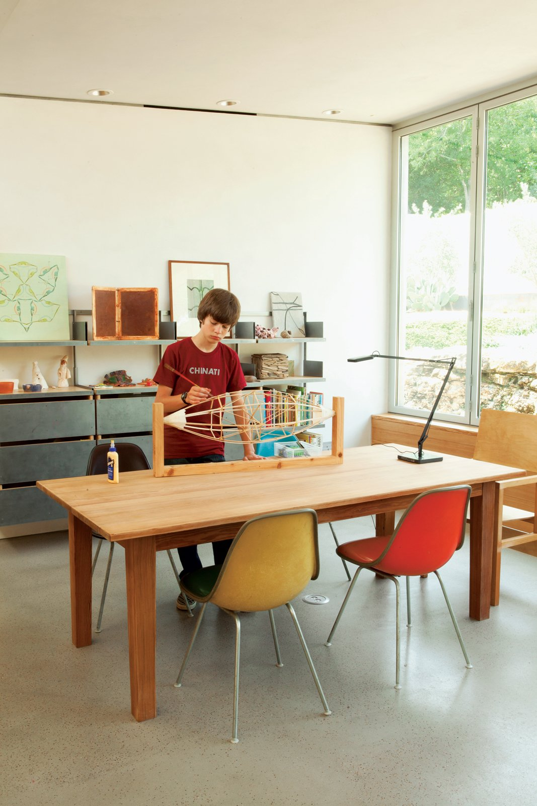 James works on his balsa-wood blimp in the family workspace, illuminated by a Kelvin LED Table Lamp from Flos. Tagged: Living Room and Chair.  Photo 3 of 10 in Hillside Mid-Century Home Renovation in Texas