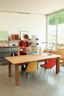 Hillside Mid-Century Home Renovation in Texas - Photo 3 of 10 - James works on his balsa-wood blimp in the family workspace, illuminated by a Kelvin LED Table Lamp from Flos.