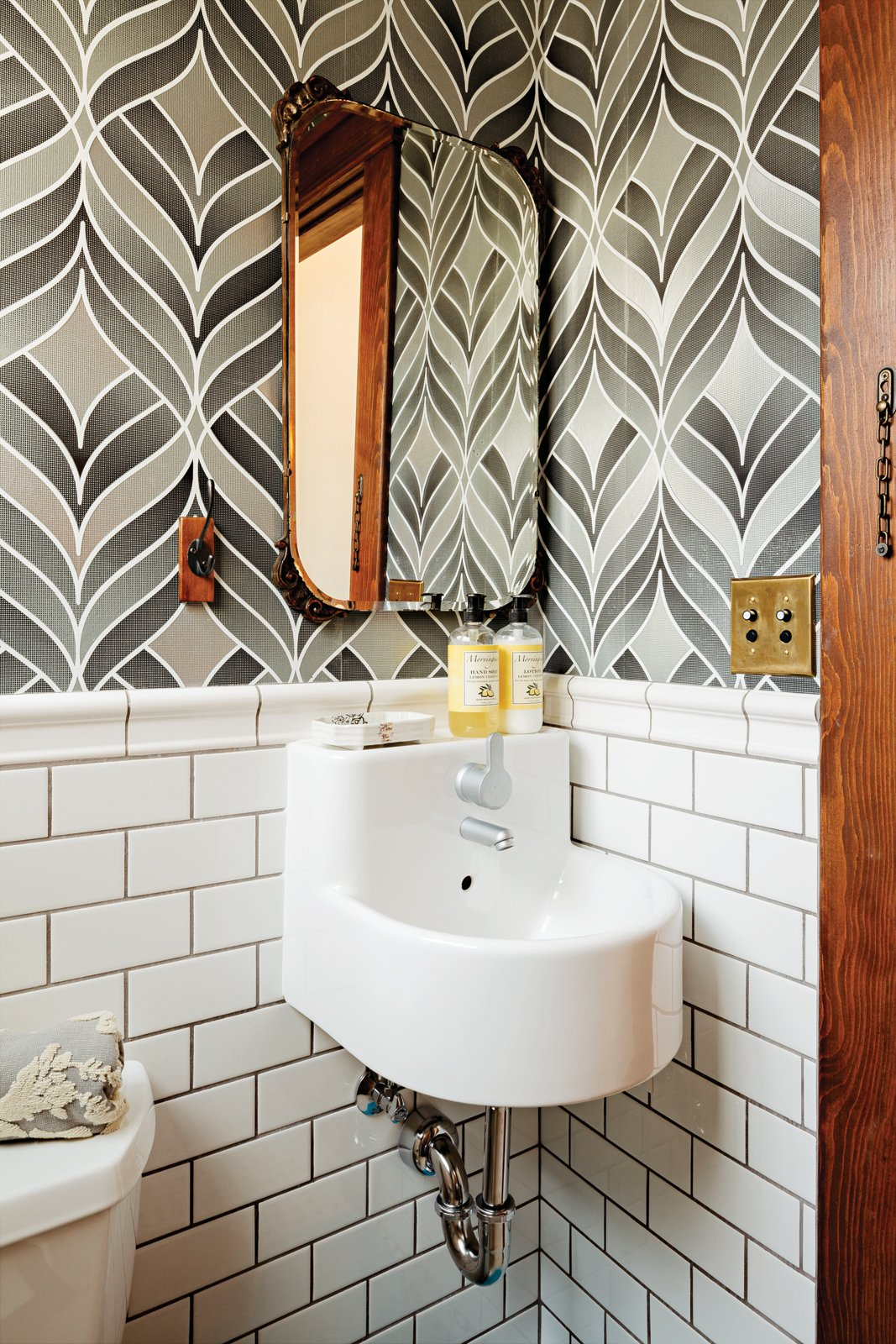 Playful wallpaper from Graham & Brown livens up the house's otherwise staid   powder room, which also contains a   pint-size Ikea sink. Tagged: Bath Room, Wall Mount Sink, and Subway Tile Wall.  Photo 17 of 42 in Wallpaper That Fixes Walls