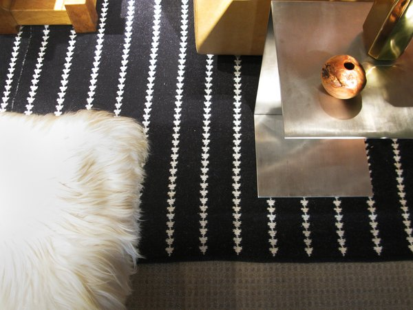 """""""There is something so memorable about 70's inspired design,"""" Berkus says. <br><br>He balances the """"metallic sheens and edginess"""" of an aluminum side table with a crisp, graphic carpet and the softness of fur."""