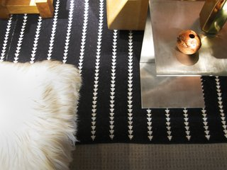 """There is something so memorable about 70's inspired design,"" Berkus says. <br><br>He balances the ""metallic sheens and edginess"" of an aluminum side table with a crisp, graphic carpet and the softness of fur."
