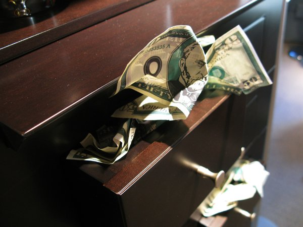 """Fake money was crammed into drawers and filled a large vessel sitting under a neon """"Money Orders"""" sign. """"My three-year-old and six-year-old assisted me in photocopying their toy money, cutting it up, and crumbling it,"""" D'Haene explains. """"It was a Sunday project. It was a lot of fun."""""""